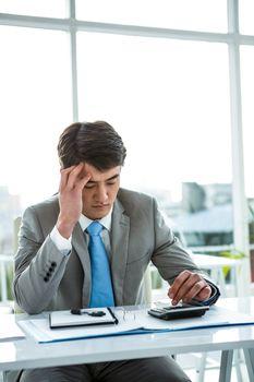 Troubled businessman using calculator