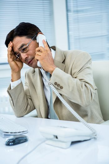 Troubled asian businessman on the phone