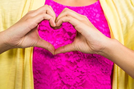 Midsection of woman with heart shape made from fingers