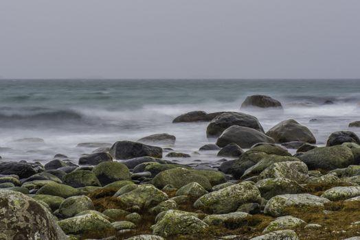 Bølger kommer inn mot Skadberg med snøbyer ute i havet.