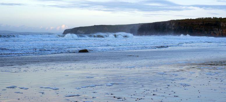 winter waves crashing onto the beach cliffs at ballybunion