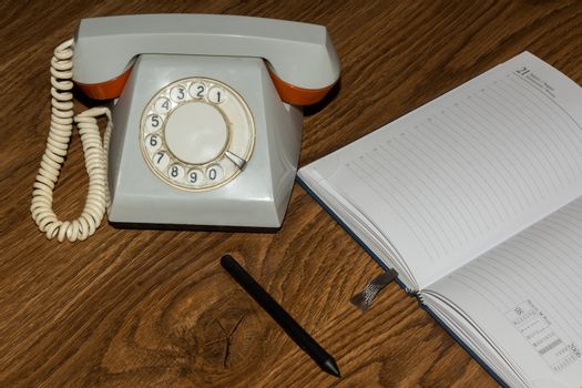 The photo depicts a landline phone with a notebook