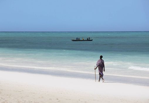 Zanzibar, Tanzania - January 6, 2016: Young massai man with colorful traditional clothes, headdress and self made shoes walking through the water on the Nungwi beach.
