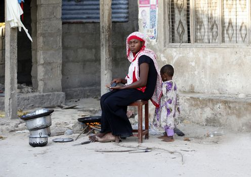 Zanzibar, Tanzania - January 9, 2016: African Muslim woman to cooks near his house, her child is playing nearby. Traditional situation for Zanzibar