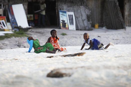 Zanzibar, Tanzania - January 9, 2016: Three African girls play on the beach and laughing on Zanzibar