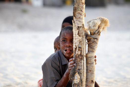Zanzibar, Tanzania - January 9, 2016: Three African children playing hide and seek on the beach on Zanzibar