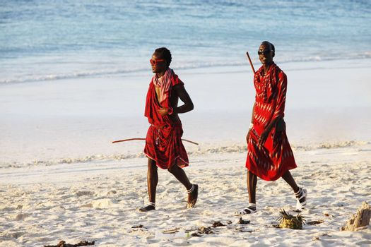 Zanzibar, Tanzania - January 5, 2016: Young massai man with colorful traditional clothes, headdress and self made shoes walking through the water on the Nungwi beach.