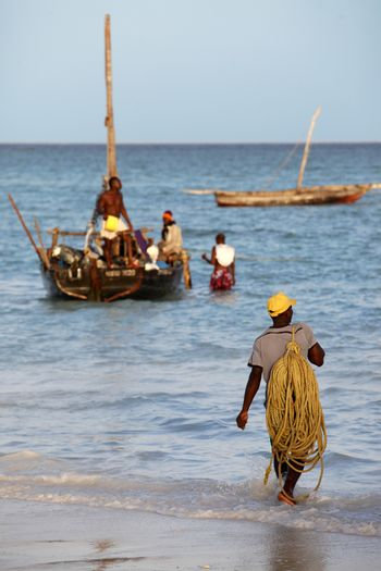 Stone Town (Zanzibar), Tanzania - January 6, 2016: A dhow (traditional sailboat) in the background and a crowded fishing boat and fishman in the foreground in the Indian Ocean just off the island of Zanzibar, Nungwi