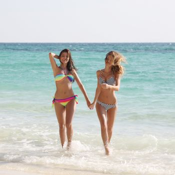 Happy smiling female friends in bikini on vacation