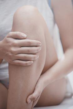 Woman doing leg massage and applying moisturizing cream