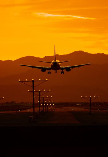 Airplane Travel at Sunset. Airliner Landing in Las Vegas Nevada During Scenic Sunset.