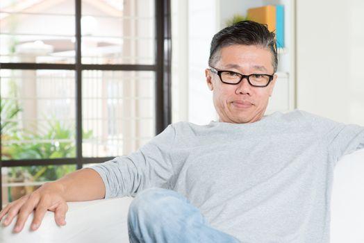 Mature 50s Asian man sitting at home.