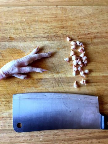 Chicken feet on cutting board with toenails cut off.