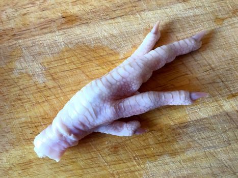 One raw chicken foot on a cutting board.