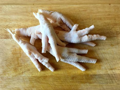 Chicken feet without toenails on a cutting board.