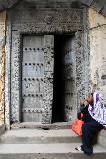 Stone Town, Tanzania - January 1, 2016: Traditional house with old door and woman in traditional Muslim clothes sitting on the street of Stone Town.