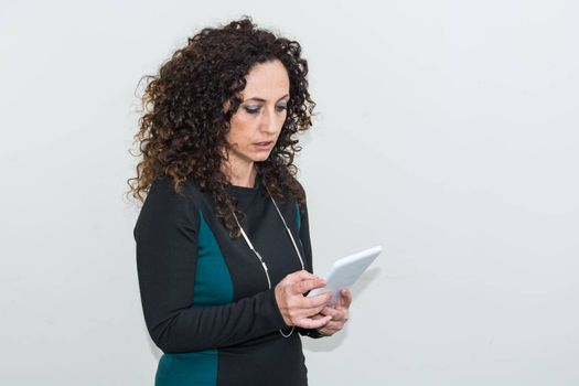 Modern mature woman, angry, use the tablet. She has long curly hair and blacks, with green eyes. Enraged, he gets angry with his work tool.