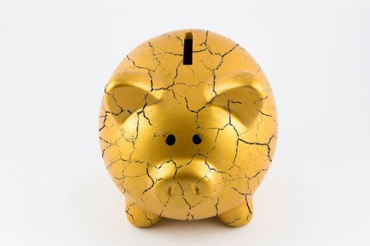 Front side of gold piggy bank cracked on isolated white background