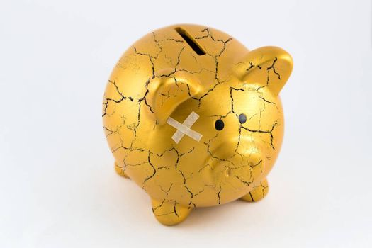 Right side of gold piggy bank cracked with plaster on isolated white background