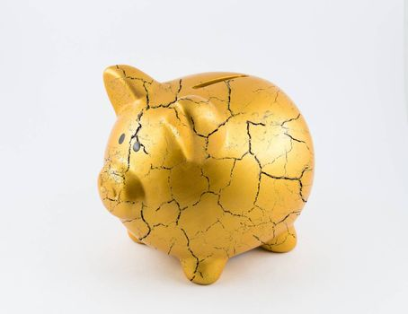 Left side of gold piggy bank cracked on isolated white background