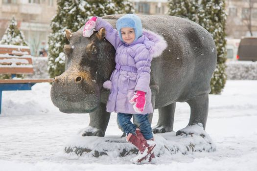 "Volgograd, Russia - January 22, 2016: Five-year girl stands the sculpture ""Hippopotamus"" sculptor Zurab Tsariteli at the entertainment center ""Gippopo"" in Krasnoarmeysk district of Volgograd"