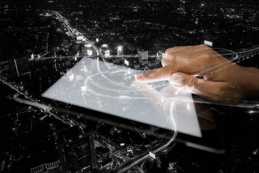 double exposure hand using tablet and city on night background