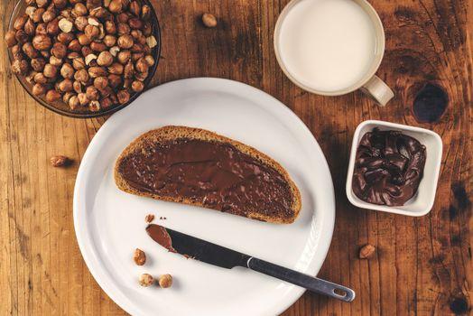 Hazelnut nougat cream spread over bread slice