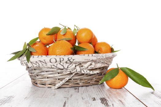 Mandarine fruit in white wooden basket on white wooden table. Provence style.