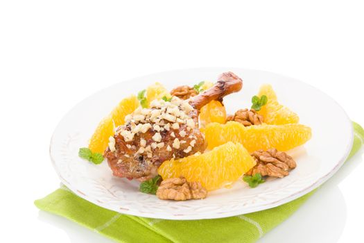 Culinary roast duck with oranges and nuts on plate isolated on white background. Delicious festive eating.