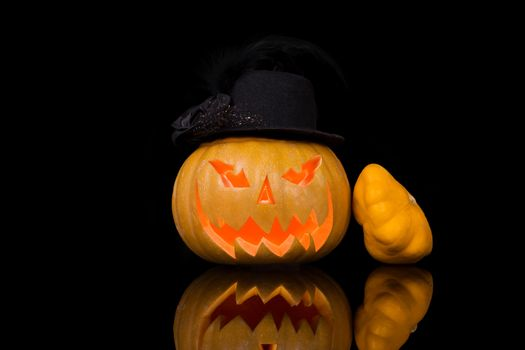 Creepy halloween pumpkin with hat isolated on black background. Traditional american halloween decoration.