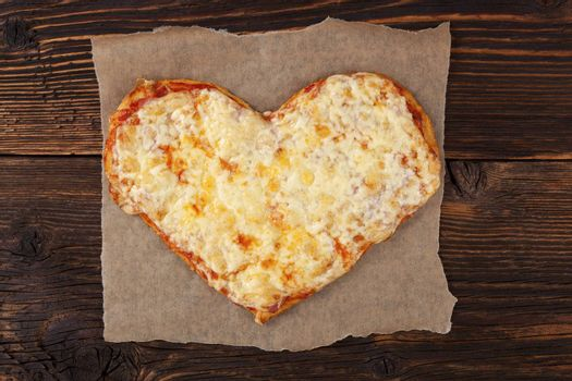 Delicious pizza in heart shape on wooden table, top view. Culinary pizza eating.