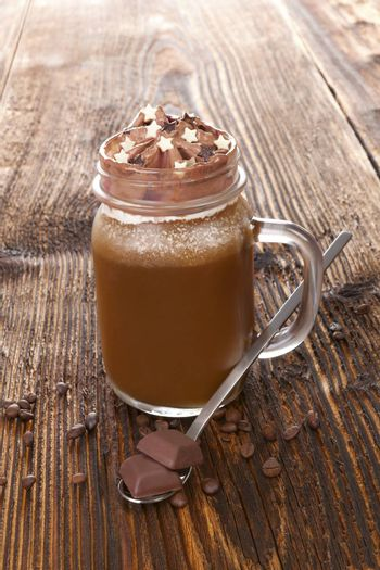 Hot chocolate with coffee beans and chocolate on wooden table. Delicious cocoa drink.