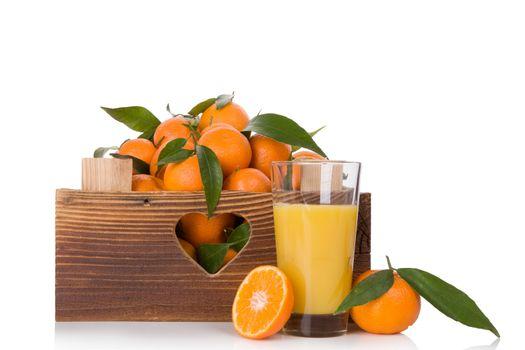 Fresh juice and ripe mandarines with green leaves in wooden crate. Organic fresh mandarines, healthy fruit eating.