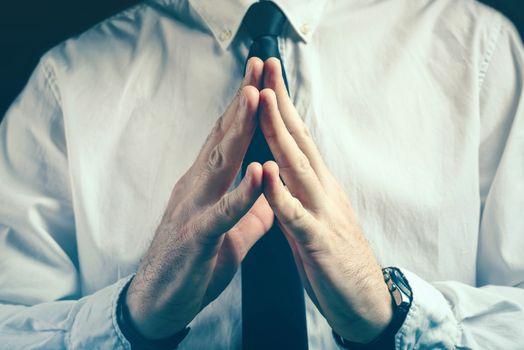 Confident businessman steepleing gesture