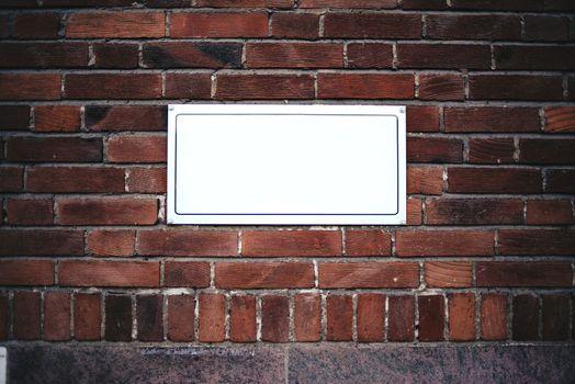 Blank street name board on brick wall