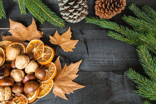 Composition of cutlery on wood background for branches and a decorative nuts, dry oranges, pain fruit and leafs for informal dinners or family celebrations in autumn winter season