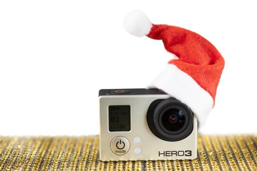 GoPro Hero 3 on golden pattern surface with a santa hat.
