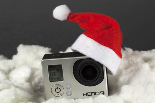 Camera with santa hat surrounded by white cotton