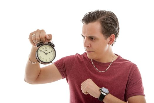 Young man is angry at alarm clock over white background