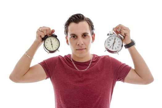 Young man is holding two alarm clocks at 6 o'clock over white background