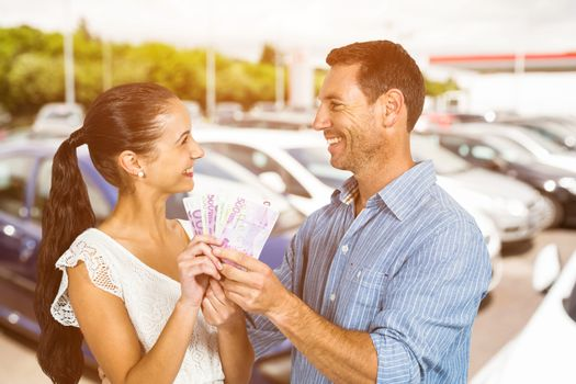 Smiling couple holding money against view of row new car