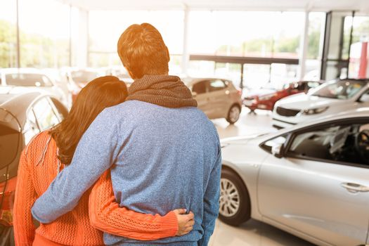 Rear view of couple against white background against view of row new car