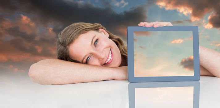 Woman showing tablet pc  against blue and orange sky with clouds