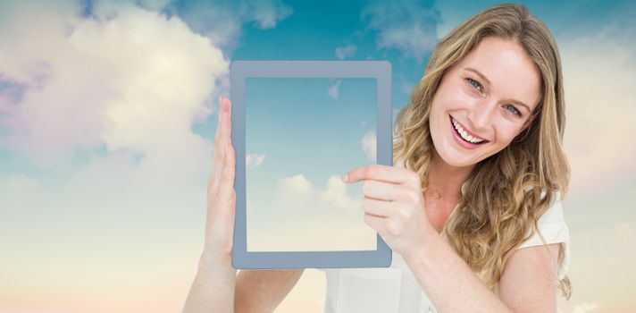 Woman showing tablet pc  against blue sky with white clouds