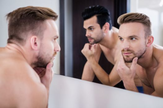 Unsmiling men in front of mirror