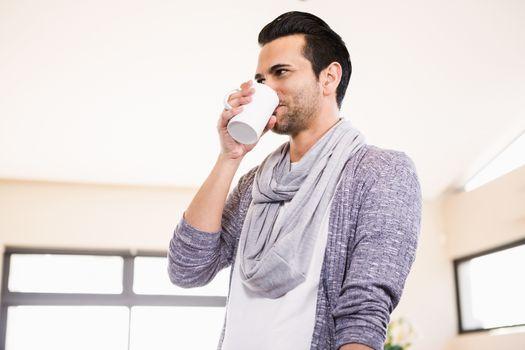 Handsome man drinking hot beverage