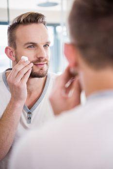 Smiling man shaving his beard
