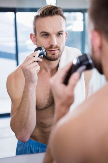 Concentrated man shaving his beard