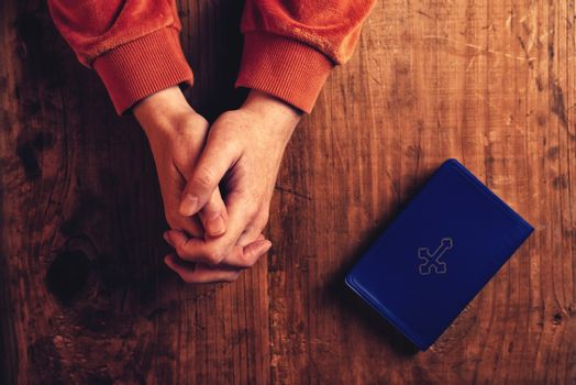 Christian woman praying with hands folded
