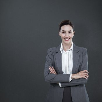Composite image of portrait of beautiful businesswoman standing arms crossed